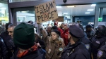 Protesters are surrounded by police officers and travellers as they pass through an exit of Terminal 4 at John F. Kennedy International Airport in New York, after earlier in the day two Iraqi refugees were detained while trying to enter the country on Jan. 28, 2017. (AP / Craig Ruttle)