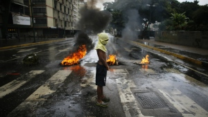 A masked protester stands near a burning barricade in Caracas, Venezuela on Wednesday, June 28, 2017. (AP / Ariana Cubillos)