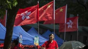 A man stands near Chinese and Hong Kong flags at an event to show support for the Chinese president's visit at a gathering in Hong Kong on Thursday, June 29, 2017. (AP / Ng Han Guan)