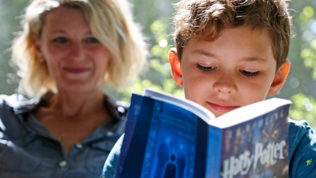 Theo Galkin, 8, rereads a favorite part of 'Harry Potter and the Sorcerer's Stone' while posing for a picture with his mother Chloe Galkin at their home in South Orange, N.J., Wednesday, June 28, 2017. (AP Photo/Seth Wenig)