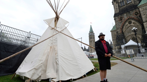 A man stands outside a large teepee erected by indigenous demonstrators to kick off a four-day Canada Day protest in front of Parliament Hill in Ottawa on Thursday, June 29, 2017. THE CANADIAN PRESS/Justin Tang
