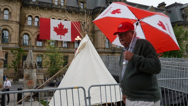 The Office of the Prime Minister and Privy Council is seen behind as a man walks past a large teepee erected by indigenous demonstrators to kick off a four-day Canada Day protest in front of Parliament Hill in Ottawa on Thursday, June 29, 2017. THE CANADIAN PRESS/Justin Tang
