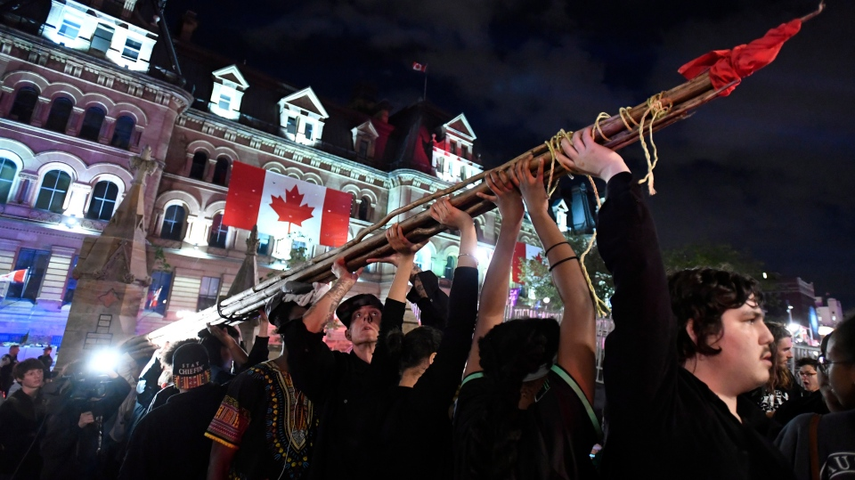 People hold a teepee, intended to be erected on Parliament Hill as part of a four-day Canada Day protest during a demonstration in Ottawa on Thursday, June 29, 2017. (Justin Tang/The Canadian Press)