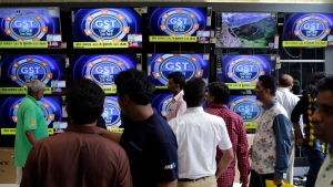 People look at televisions inside an electronics shop, a day ahead of the implementation of the nationwide Goods and Services Tax (GST) in Mumbai, India, Friday, June 30, 2017. (AP Photo/Rajanish Kakade)