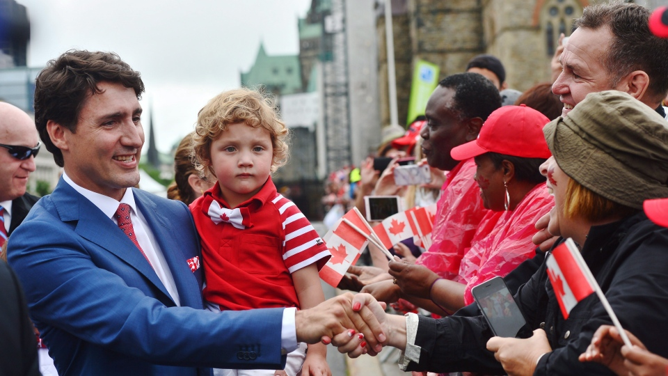 Prime Minister Justin Trudeau and his son Hadrien, greet people during Canada 150 celebrations in Ottawa on Saturday, July 1, 2017. (THE CANADIAN PRESS/ Sean Kilpatrick)