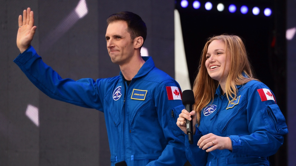 Canada's newest astronauts Joshua Kutryk and Jennifer Sidey acknowledge the crowd during Canada 150 celebrations on Parliament Hill in Ottawa on Saturday, July 1, 2017. (THE CANADIAN PRESS/ Sean Kilpatrick)
