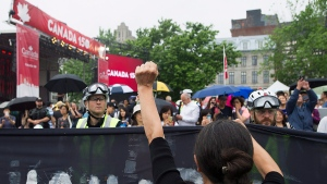 Police hold back demonstraters during a protest in Montreal, Saturday, July 1, 2017. THE CANADIAN PRESS/Graham Hughes
