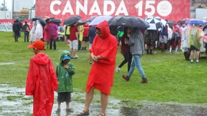 People stand in puddles as they take in the Canada 150 celebrations on Parliament Hill in Ottawa on Saturday, July 1, 2017. (Fred Chartrand / THE CANADIAN PRESS)