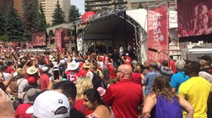 Crowd at Olympic Plaza watches as Ian Tyson leads a group of hundreds of guitarists in a performance
