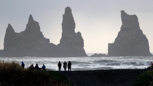 People walk on the black sanded beach in Vik, Iceland, near the Volcano Katla, Wednesday, Oct. 26, 2016. (AP Photo/Frank Augstein)