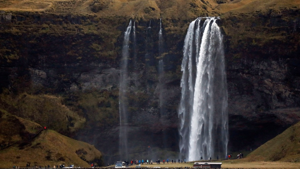 People watch a waterfall near Vik, Iceland, near the Volcano Katla, Friday, Oct. 28, 2016. (AP Photo/Frank Augstein)