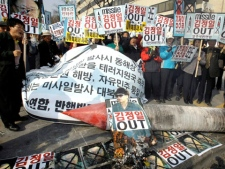 South Korean protesters burn placards bearing pictures of North Korean leader Kim Jong Il and mock missile during a rally against North Korea's missile launch near the U.S. Embassy in Seoul, South Korea, Sunday, April 5, 2009. (AP / Lee Jin-man)