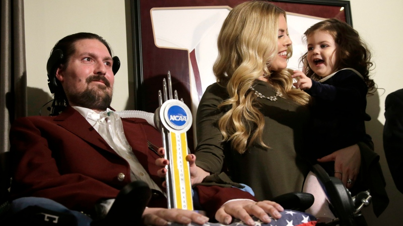 In this Dec. 13, 2016, file photo, former Boston College baseball captain Pete Frates, left, appears with his wife Julie, center, and two-year-old daughter Lucy, right, moments after he was presented with the 2017 NCAA Inspiration Award, at their home in Beverly, Mass. (AP / Steven Senne)