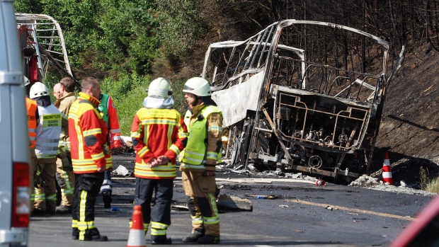 Rescue workers and fire fighters stand beside a burnt-out coach on the motorway A9 near Muenchberg, southeastern Germany, Monday, July 3, 2017 after a bus crashed into a truck and caught fire. (Nicolas Armer/dpa via AP)