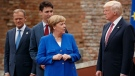 In this May 26, 2017 file photo, German Chancellor Angela Merkel, accompanied by European Council U.S. President Donald Tusk, Canadian Prime Minister Justin Trudeau, talks with President Donald Trump during a family photo with G7 leaders at the Ancient Greek Theater of Taormina in Taormina, Italy.