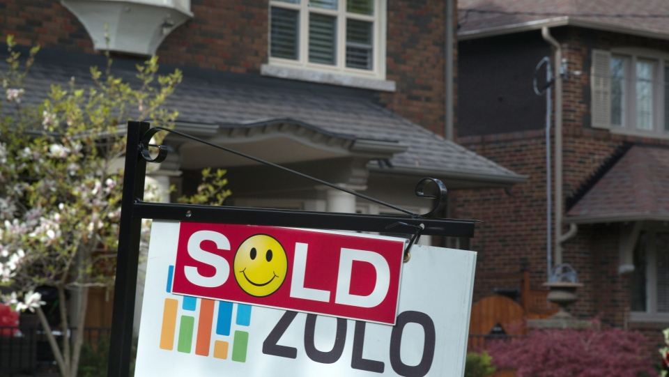A sold sign is shown in front of west-end Toronto homes, Sunday, May 14, 2017. (Graeme Roy / THE CANADIAN PRESS)