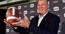 Randy Ambrosie tosses a football as he speaks during a press conference in Toronto, Wednesday July 5, 2017. The CFL says Ambrosie will serve as the 14th commissioner in league history. (Frank Gunn /  THE CANADIAN PRESS)