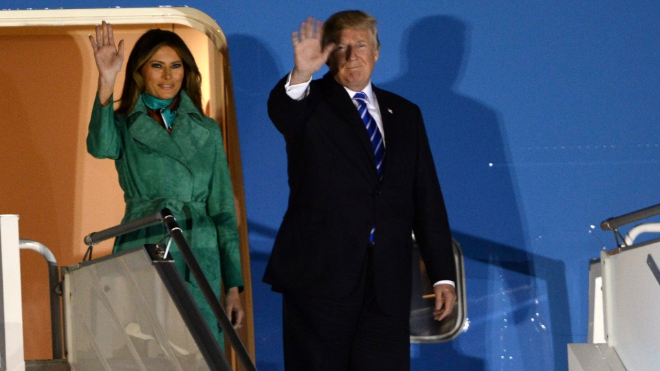 U.S. President Donald Trump and first lady Melania Trump wave from the Air Force One upon their arrival Warsaw, Poland, Wednesday, July 5, 2017. (AP Photo/Alik Keplicz)