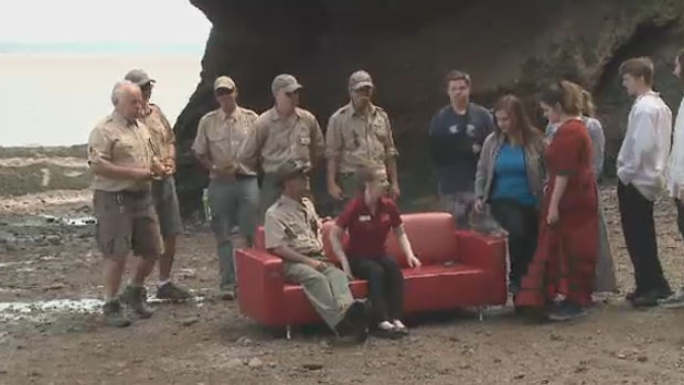 Tourists gather on the couch to explain what Canada means to them.