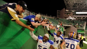 Winnipeg Blue Bombers linebacker Kyle Knox, left, defensive end Tristan Okpalaugo, centre, and offensive lineman Michael Couture, right, celebrate with fans after an overtime win over the Saskatchewan Roughriders at the brand new Mosaic Stadium, in Regina on Saturday, July 1, 2017. (Source: Mark Taylor/The Canadian Press)