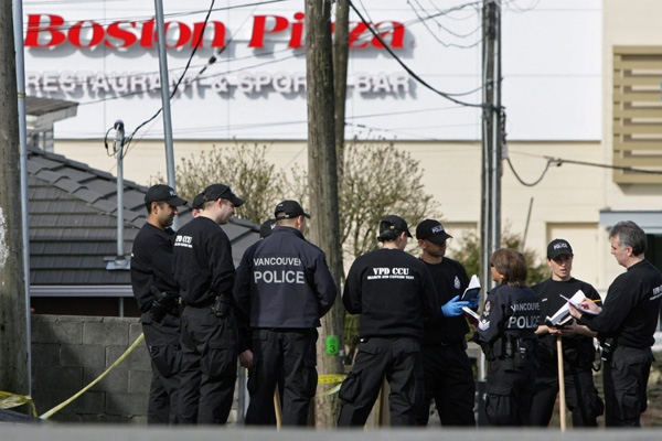 Police officers gather in a nearby alley as they search for evidence following a fatal shooting outside a Boston Pizza restaurant at Grandview Hwy. and Bentall St. in Vancouver, B.C., on Sunday April 5, 2009. (CP/Darryl Dyck)