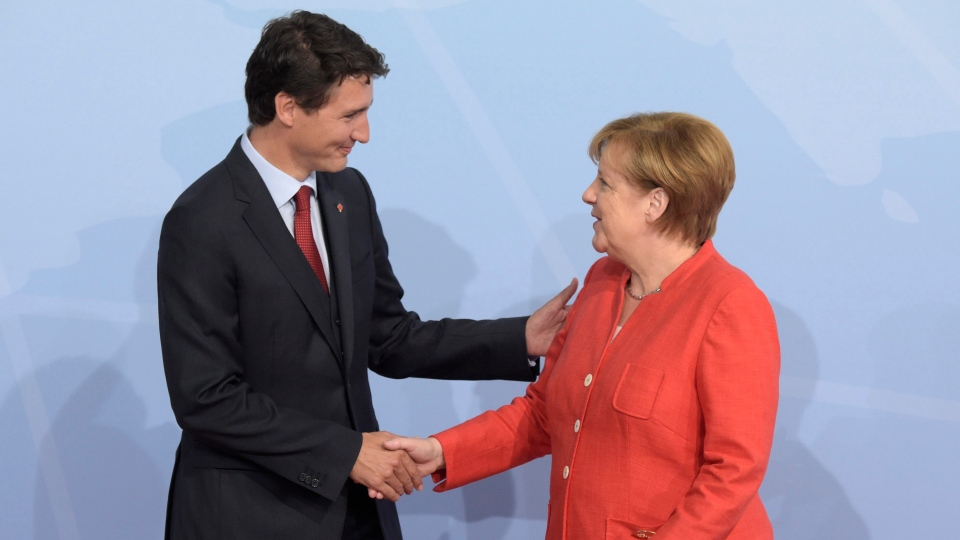 Prime Minister Justin Trudeau, left, is welcomed by German Chancellor Angela Merkel on the first day of the G-20 summit in Hamburg, northern Germany, Friday, July 7, 2017. (Jens Meyer/AP)