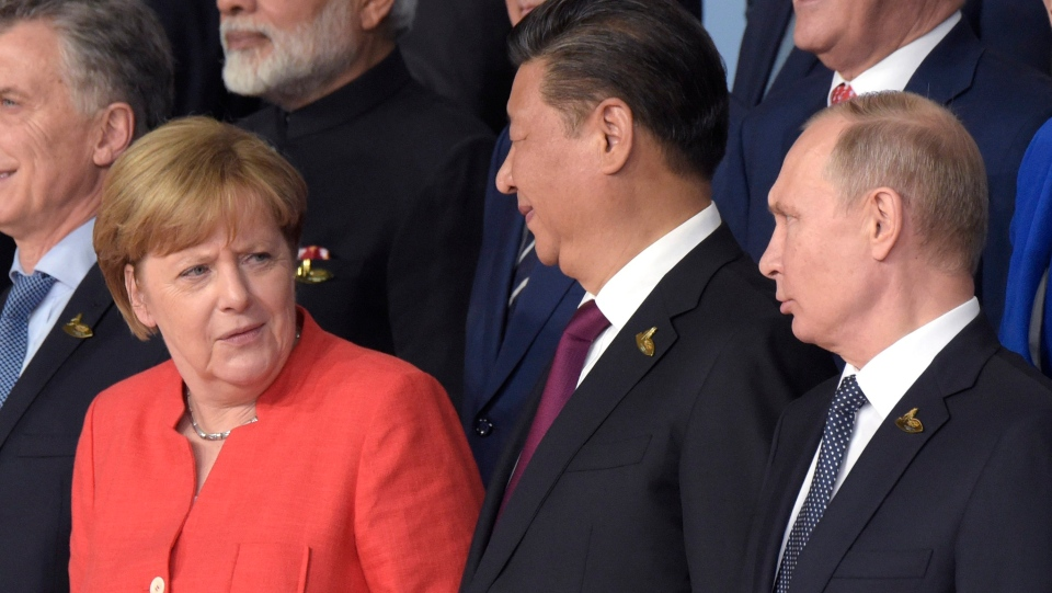 German Chancellor Angela Merkel talks to Russian President Vladimir Putin, right, and Chinese President Xi Jinping, centre, during the family photo on the first day of the G-20 summit in Hamburg, northern Germany, Friday, July 7, 2017. (AP Photo/Jens Meyer)