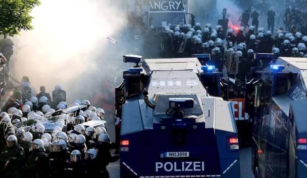Police officers stay next to water cannons during a protest against the G-20 summit in Hamburg, northern Germany, Thursday, July 6, 2017. The leaders of the group of 20 meet July 7 and 8. (AP Photo / Michael Probst)