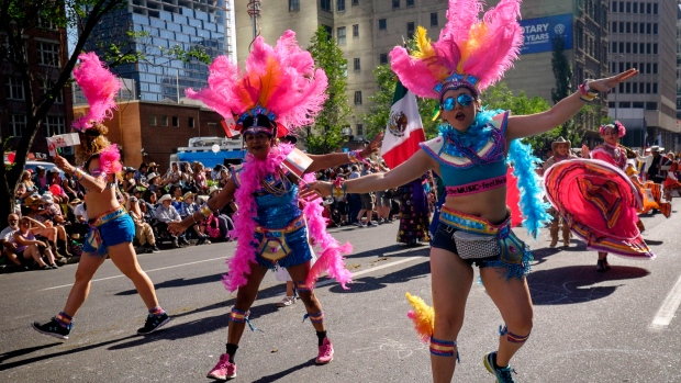 Marchers dance during the Calgary Stampede parade. (THE CANADIAN PRESS / Jeff McIntosh)