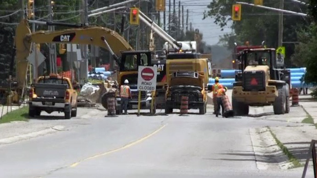 Construction crews work at Sawmill Road and Northfield Drive on Friday, July 7, 2017.