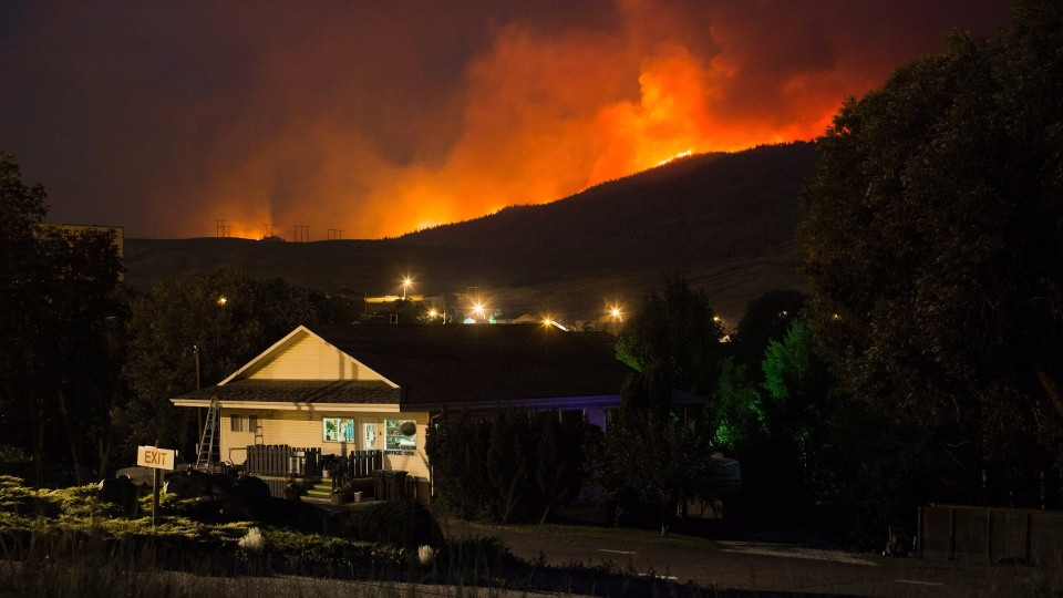 A wildfire burns on a mountain behind an RV park office in Cache Creek, B.C., in the early morning hours of Saturday July 8, 2017. THE CANADIAN PRESS/Darryl Dyck