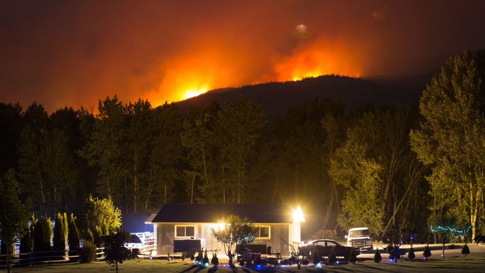 A wildfire burns on a mountain behind a home in Cache Creek, B.C., in the early morning hours of Saturday July 8, 2017. (Darryl Dyck / THE CANADIAN PRESS)