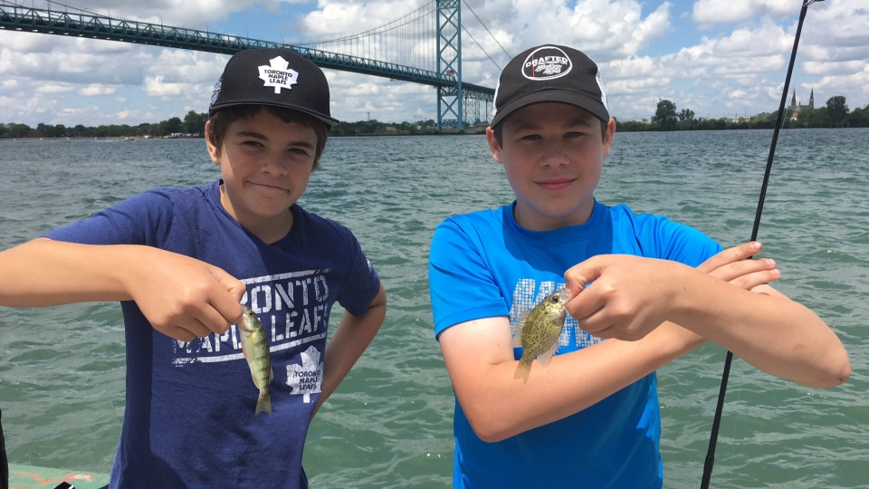 Two boys show off their fish on the Detroit River in Windsor, Ont., on Saturday, July 8, 2017. (Melanie Borrelli / CTV Windsor)