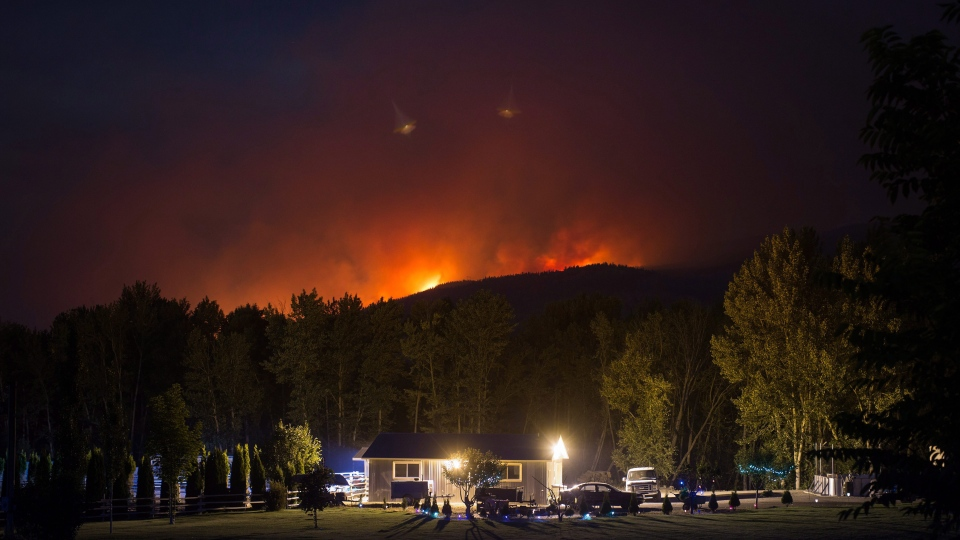 A wildfire burns on a mountain behind a home in Cache Creek, B.C., in the early morning hours of Saturday July 8, 2017. (Friday. THE CANADIAN PRESS/Darryl Dyck)