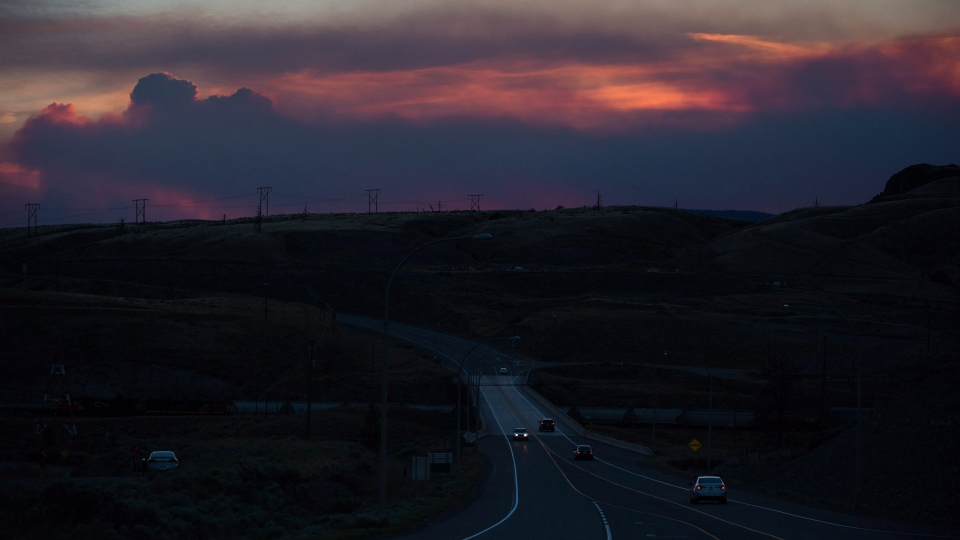 Motorists travel on the Trans-Canada Highway in Savona, B.C., as smoke from a wildfire burning near Ashcroft rises in the distance at sunset on Friday July 7, 2017. THE CANADIAN PRESS/Darryl Dyck