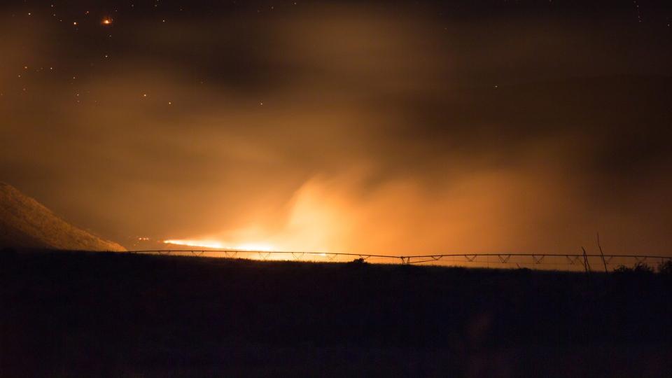 A wildfire burns behind irrigation equipment on a farm near Ashcroft, B.C., late Friday July 7, 2017. THE CANADIAN PRESS/Darryl Dyck