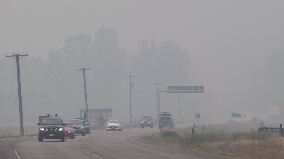 Smoke from wildfires blankets the area as motorists travel on the Yellowhead Highway in Little Fort, B.C., on Saturday July 8, 2017. (THE CANADIAN PRESS/Darryl Dyck)