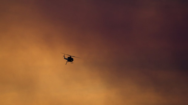 A firefighting helicopter flies past smoke in the air from a wildfire burning near Ashcroft, B.C., at sunset on Friday July 7, 2017. THE CANADIAN PRESS/Darryl Dyck