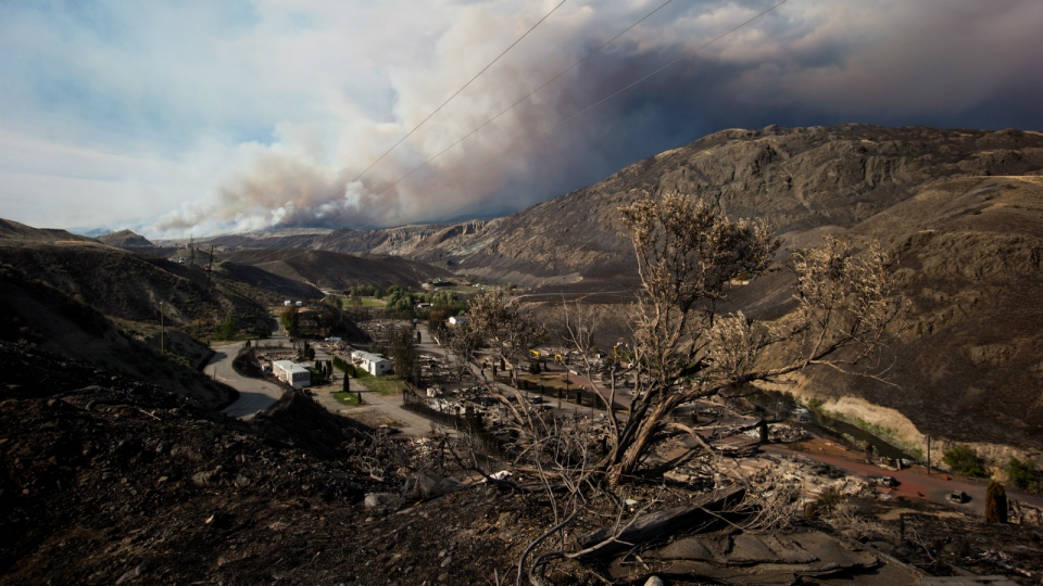 A burnt tree is seen in the foreground above the remains of mobile homes destroyed by wildfire in Boston Flats as a fire burns on a mountain near Ashcroft, B.C., on Sunday, July 9, 2017. (Darryl Dyck / THE CANADIAN PRESS)