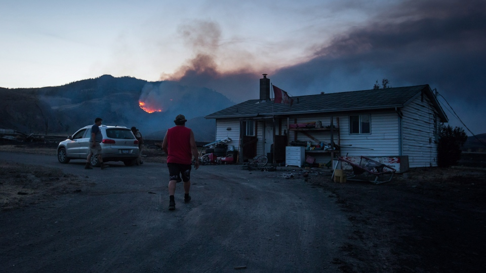 Darin Minnabarriet walks to his house that survived a wildfire to empty his freezer on the Ashcroft First Nation, as a fire burns on a mountain in the distance near Ashcroft, B.C., late Sunday, July 9, 2017. THE CANADIAN PRESS/Darryl Dyck