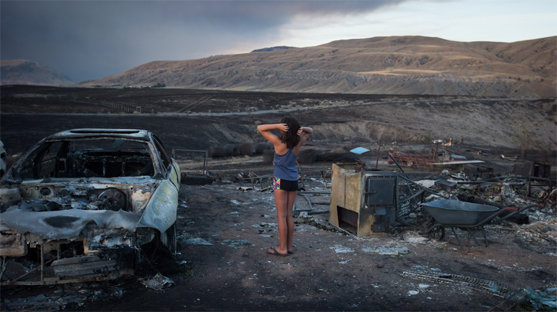 Nevaeh Porter, 8, reacts while viewing the remains of her home where she lived with her mom and grandparents that was destroyed by wildfire on the Ashcroft First Nation, near Ashcroft, B.C., late Sunday, July 9, 2017. THE CANADIAN PRESS/Darryl Dyck