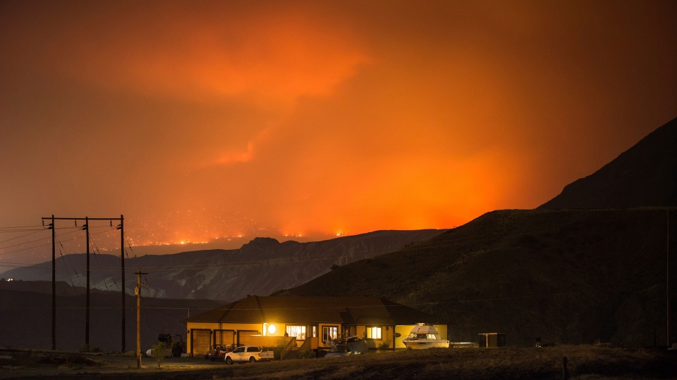 A wildfire burns on a mountain in the distance east of Cache Creek behind a house in Boston Flats, B.C., in the early morning hours of Monday July 10, 2017. (Darryl Dyck/The Canadian Press)