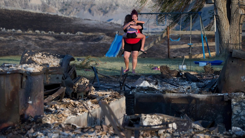 Kelsey Thorne holds her daughter Nevaeh Porter, 8, as they both cry while viewing the remains of their home where they lived with her parents that was destroyed by a wildfire on the Ashcroft First Nation, near Ashcroft, British Columbia, late Sunday, July 9, 2017. (Darryl Dyck/The Canadian Press via AP)