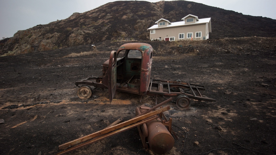 The burned remains of a vintage truck sit in front of a house that survived a wildfire in Boston Flats, B.C., on Monday, July 10, 2017. (THE CANADIAN PRESS/Darryl Dyck)