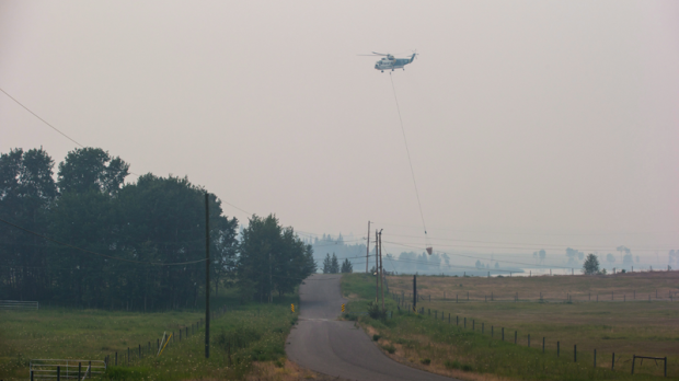 A helicopter lifts off after picking up water while battling the Gustafsen wildfire near 100 Mile House, B.C., on Saturday July 8, 2017. Residents of 100 Mile House and the surrounding area were allowed to return on Saturday, July 22, 2017. (THE CANADIAN PRESS/Darryl Dyck)