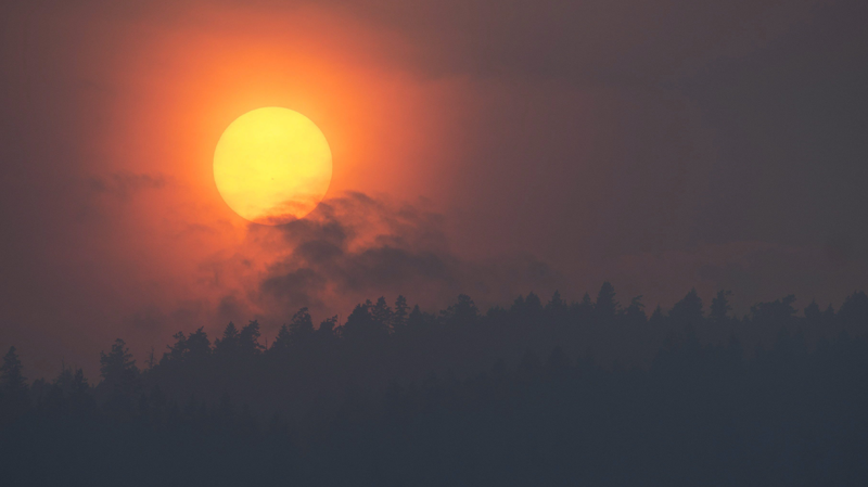 Smoke is seen rising in front of the sun as a wild fire burns near Little Fort, B.C. Tuesday, July 11, 2017. (THE CANADIAN PRESS/Jonathan Hayward)