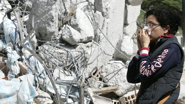 A woman reacts after firefighters pulled out a body from the rubble of a collapsed building, in L'Aquila, Italy, in this April 2009 file photo. (AP / Gregorio Borgia)