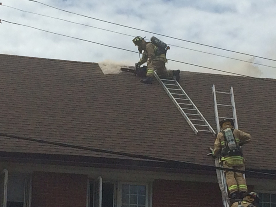 Firefighters cut through roof to fight flames