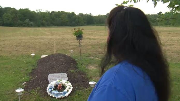 Roxanne Farmer looks at the grave of her son, Dustin Monture, who was shot dead in February 2017.