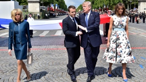 French President Emmanuel Macron, second left, shakes hands with U.S President Donald Trump on the Champs Elysees in Paris, on July 14, 2017. (Christophe Archambault, Pool via AP)